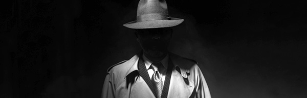 Faceless man in trench coat and hat standing in dimly lit room