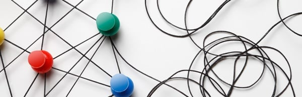 Black string connected to several different colored push pins